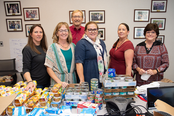 Group photograph of ASWB staff with food items collected for charity