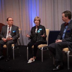 Photograph of three people seated in chairs on a stage