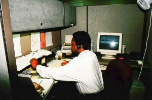 Photograph of a man in an office cubicle wearing a telephone headset