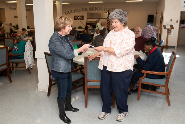 Photograph of Mary Jo Monahan handing a check to the manager of the Culpeper Senior Center