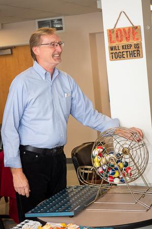 Photograph of Dwight Hymans turning a hand-cranked bingo machine
