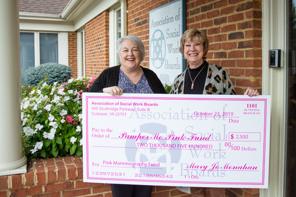 Photograph of two women holding a large novelty check