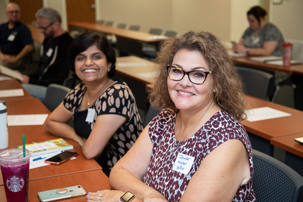 Photograph of two smiling women in a conference room