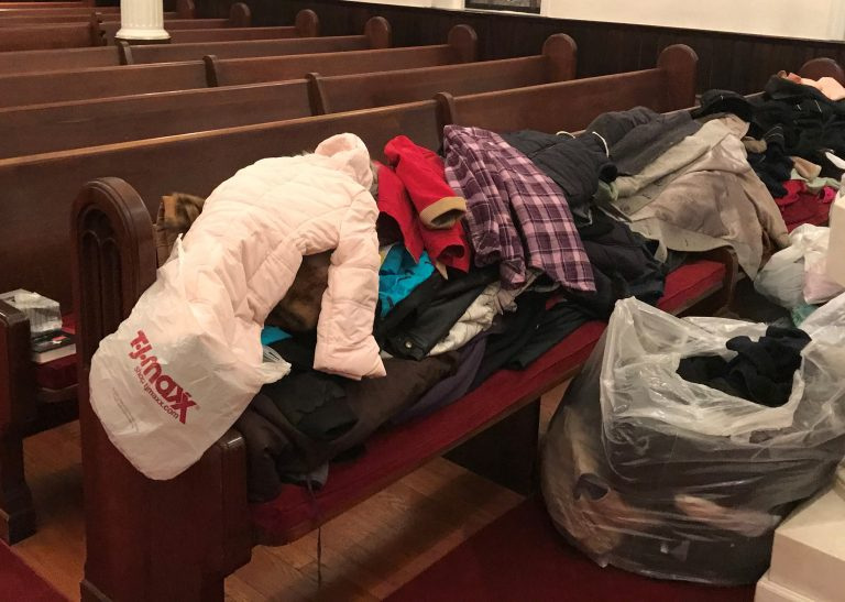 Photograph of dozens of winter coats spread out on a church pew
